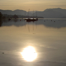 Sun and boats reflected in Ullswater on beautiful calm Autumn evening