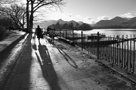 Black and white image of a woman walking her dog beside Derwentwater near Keswick Boat Landings with Catbells in background
