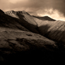 Dramatic image of Blencathra or Saddleback with Halls Fell Ridge and crags lit by evening sun, with rest of mountain in shadow