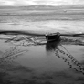 Footprints in mud leading to and from Fishing boat at low tide in Morecambe Bay. Southern Lake District seen in distance