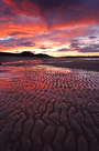 Fiery sunset relected in wet sands sands of Embleton Bay